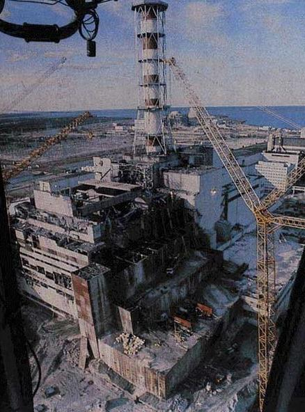 The Chernobyl nuclear plant in Ukraine, apparently after they started to build the sarcophagus in the aftermath of the disaster. The nuclear disaster itself had happened on 26 of April 1986. Compare with photo just following this one. When comparing, take the red-and-white chimney as point of reference for orientation.