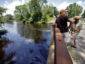 Déversement de pétrole dans la rivière Kalamazoo au Michigan, ÉU. En 2010. Le pétrole coüte de plus en plus cher, ça appauvrit et ça entraîne la détérioration des infrastructures par manque de fonds et négligence, et ça se perd de plus en plus en empoisonnant notre assise vitale : le top, l'eau, les plantes..