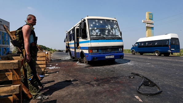 An armed anti-goverment fighter stands guard near a bus riddled with bullet holes at a checkpoint on the outskirts of Donetsk, August 13, 2014 (Reuters / Sergey Karpukhin)