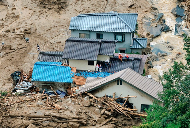 Local residents wait for rescue operation atop of collapsed houses as rescue workers stand by next to them, after a massive landslide swept through a residential area at Asaminami ward in Hiroshima, western Japan, in this photo taken by Kyodo August 20, 2014. (Reuters / Kyodo)